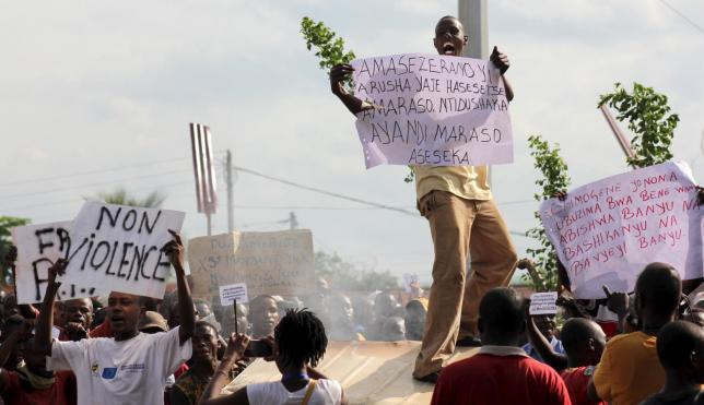 A protester carries a placard as they chant anti-government slogans during demonstrations against the ruling CNDD-FDD party's decision to allow Burundi President Pierre Nkurunziza to run for a third five-year term in office, in Bujumbura, May 4, 2015. REUTERS/Jean Pierre Aime Harerimana