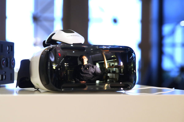 Avinash Changa, WeMakeVR's chief executive, is  reflected on the glass of the firm's Falcon virtual reality device.