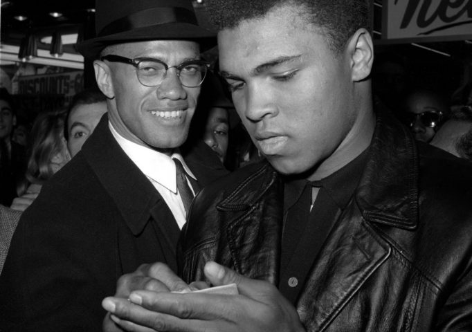 Muhammad Ali with Black Muslim Leader Malcolm X outside the Trans-Lux Newsreel Theater on Broadway, Mar. 1, 1964. They had just watched a screening of Ali's title fight with Sonny Liston in Miami Beach. AP Photo