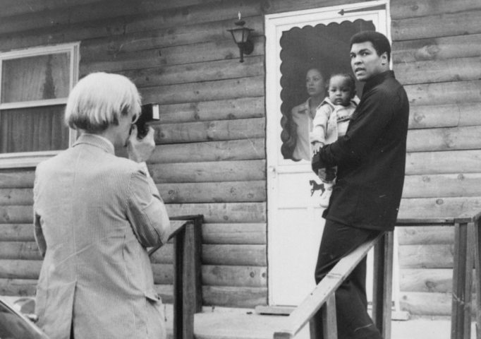 Andy Warhol photographing Muhammad Ali, his infant daughter, Hanna, and wife, Veronica, Aug. 18, 1977, at Ali's training camp in Deer Lake, Pa. AP Photo