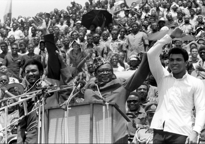 Zaire's President Mobutu Sese Seko raises the arms of heavyweight champ George Foreman and Muhammad Ali in Kinshasa, Zaire, Sept. 22, 1974, prior to the Rumble in the Jungle. In one of boxing's most memorable moments, Ali stopped the fearsome Foreman to recapture the heavyweight title. AP Photo/Horst Faas