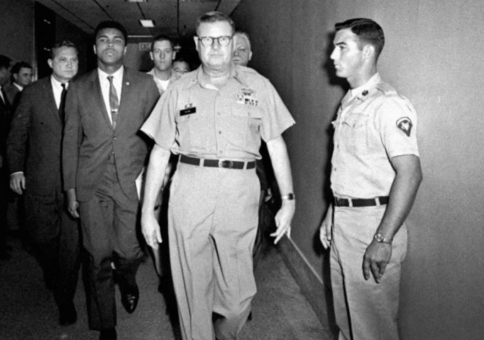 Muhammad Ali is escorted from the Armed Forces Examining and Entrance Station in Houston by Lt. Col. J. Edwin McKee, April 28, 1967, after Ali refused Army induction. Ali says he was a conscientious objector who would not serve in the Army of a country that treated members of his race as second-class citizens. AP Photo