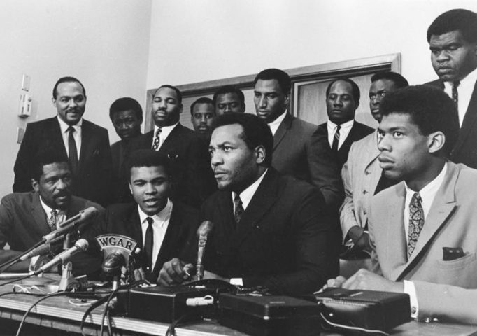A group of top African American athletes from different sporting disciplines gather to give support and hear the boxer Muhammad Ali give his reasons for rejecting the draft during the Vietnam War, at a meeting of the Negro Industrial and Economic Union, held in Cleveland, June 4, 1967. Seated in the front row, from left to right: Bill Russell, Muhammad Ali, Jim Brown, and Kareem Abdul Jabbar. Standing behind them are: Carl Stokes, Walter Beach, Bobby Mitchell, Sid Williams, Curtis McClinton, Willie Davis, Jim Shorter, and John Wooten. Robert Abbott Sengstacke/Getty Images