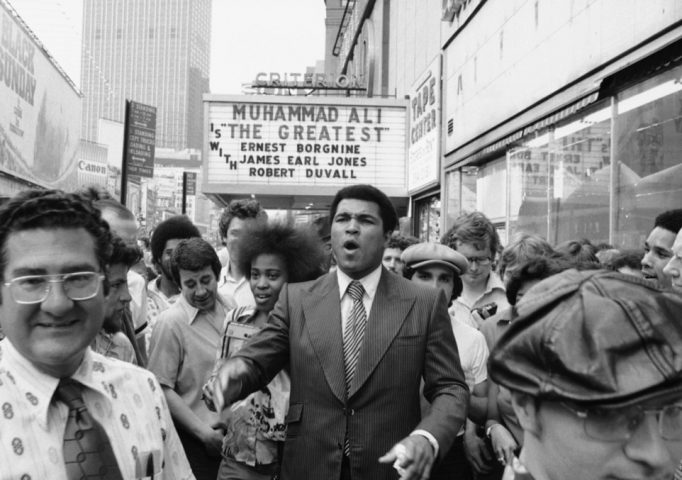 Heavyweight champ Muhammad Ali attracts a following as he walks through New York's Times Square on May 25, 1977. AP Photo