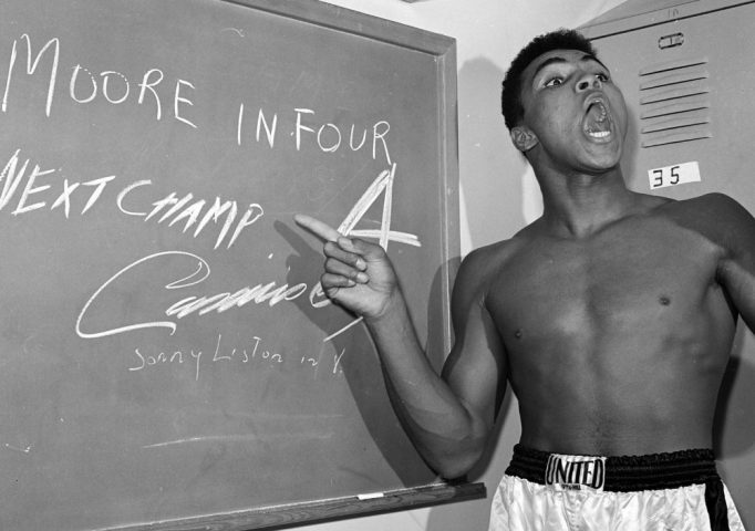 Cassius Clay points to a sign he wrote on a chalk board in his dressing room before his fight against Archie Moore in Los Angeles, Nov. 15, 1962, predicting he'd knock Moore out in the fourth round, which he went on to do. The sign also predicts Clay will be the next champ via a knockout over Sonny Liston in eight rounds. He did it in seven rounds. AP Photo/Harold P. Matosian