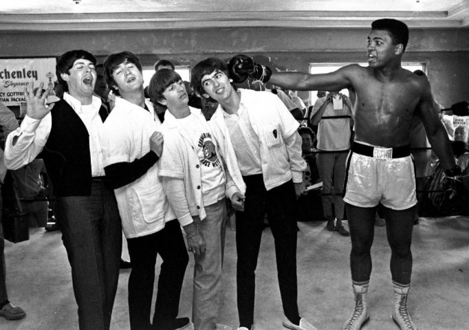 The Beatles Paul McCartney, John Lennon, Ringo Starr, and George Harrison take a fake blow from Cassius Clay at his training camp in Miami Beach, Fla. on Feb. 18, 1964. AP Photo